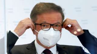 Austrian Health Minister Rudolf Anschober adjusts his face mask during a news conference in Vienna, 13 April
