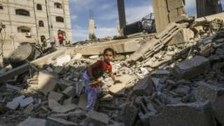 A Palestinian girl climbs on the remains of a building that was destroyed during an Israeli air strike on Rafah on 5 May 2019