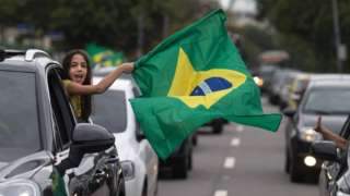 Supporters of presidential candidate for the Social Liberal Party (PSL) Jair Bolsonaro cheer in front of the residential condominium where he lives, in Barra da Tijuca, in Rio de Janeiro, Brazil, on October 7