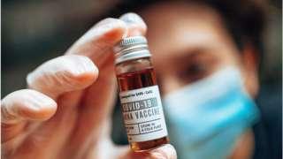 拿着新冠疫苗小瓶的药剂师