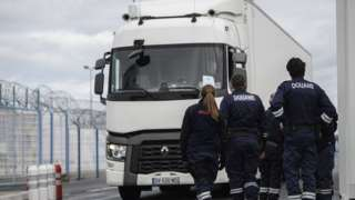 French Customs officers look on trucks arriving for embarkation at the port of Cherbourg, Normandy region, France