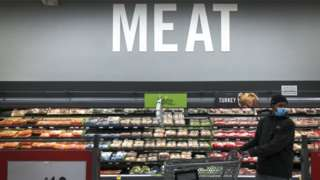 Shopper in the meat section of a supermarket in Washington, DC