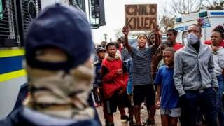"""A resident holds a placard that reads: """"Child Killer"""" next to members of the South African Police Service (SAPS) outside the SAPS offices in Eldorado Park, near Johannesburg, on August 27, 2020, during a protest by community members after a 16-year old boy was reported dead"""