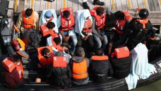 A group of people, thought to be migrants, waiting on a Border Force rib to come ashore at Dover marina