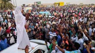 Protesters in Khartoum hold up their phones to film fellow protester Alla Salah who stands on a car dressed in a white headscarf and skirt