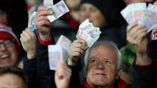 Gloucester fans waved money ate Saracens in reference to their salary cap fine