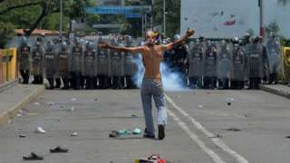 A demonstrator gestures in front of Venezuelan national policemen standing guard at the Simon Bolivar international bridge, in Cucuta, Colombia