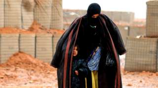 File photo: A Syrian refugee from the informal Rukban camp walks in the rain as she shelters a young child outside a UN-operated medical clinic, 1 March 2017