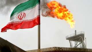 A gas flare on an oil production platform in the Soroush oil fields is seen alongside an Iranian flag in the Persian Gulf, Iran, in July 2005