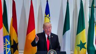 Donald Trump speaks with African flags in the background