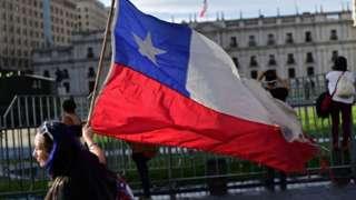 Mujer con una bandera chilena