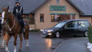 Hearse with mounted officer