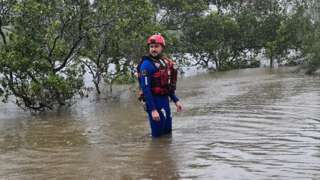 An emergency responder knee deep in floodwater in Urunga, New South Wales
