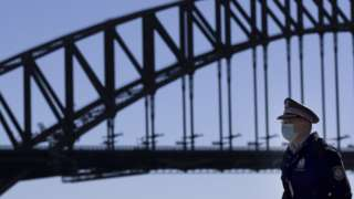 A police officer is seen near Harbour Bridge in Sydney, Australia, July 18, 2021. Rising COVID-19 cases sparked tougher restrictions with more retail closed in Australia's state of New South Wales (NSW).