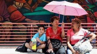 Criança senta ao lado de senhoras em uma praça em Caracas, na Venezuela