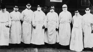 Doctors, army officers, and reporters wear surgical gowns and masks while making a tour of a hospital to observe Spanish influenza treatment of patients. -