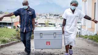 Health workers carrying vaccine box in Goma in DR Congo