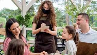 พนักงานในร้านอาหารกำลังรับแขก