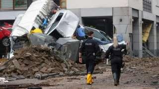 Police walk past debris in the spa town of Bad Neuenahr