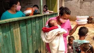 Mãe com criança de colo recebe doação de marmita em ação do MST no Paraná