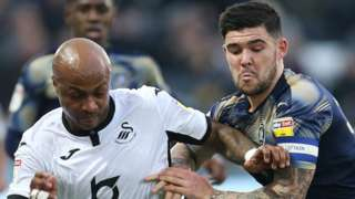 Andre Ayew of Swansea City and Alex Mowatt of Barnsley compete for the ball