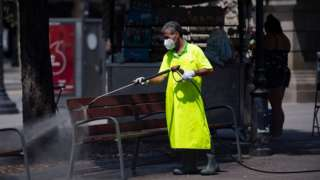 A municipal worker cleans a bench at Catalonia square in Barcelona on July 18, 2020.