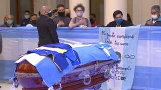 Fans walks past Maradona's coffin