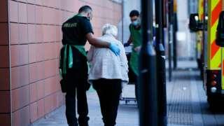 A healthcare worker leading an elderly woman