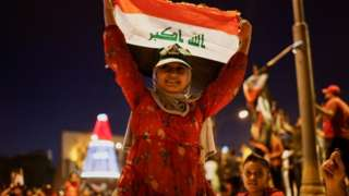 A young supporter of Shia cleric Moqtada al-Sadr holds up an Iraqi flag at a rally in Baghdad held after the initial results of Iraq's election were announced (11 October 2021)