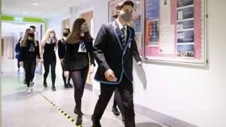 Masked pupils in school corridor