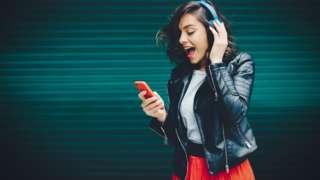 Joyful girl listening to music from smartphone