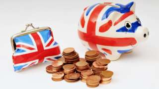 A small purse and piggy bank in Union Jack colours with a pile of UK one and two pence coins