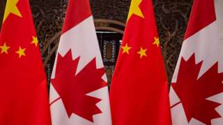 Banderas chinas y canadienses durante una reunión de los presidentes Xi Jinping y Justin Trudeau.