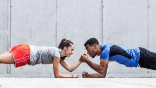 Un hombre y una mujer haciendo un ejercicio de resistencia de peso.