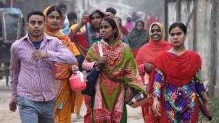 Trabajadores camino a casa tras terminar su turno laboral en una fábrica de confección en Daca, febrero 2020