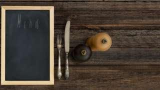 Sobre la mesa, sal, pimienta, cubiertos y un menú.