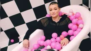 Caitlin posing in a bath (fully clothed) with pink balls all around her on a black and white background