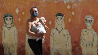 A woman wearing a face mask to prevent the spread of the coronavirus walks past a graffiti in homage to the medical staff, at the San Martin hospital, in La Plata, on the outskirts of Buenos Aires