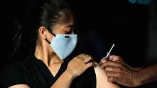 A woman reacts as she receives a dose of COVISHIELD coronavirus disease (COVID-19) vaccine manufactured by Serum Institute of India, at an auditorium that has been converted into a temporary vaccination centre in Ahmedabad, India, March 24, 2021.