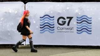英國康沃爾郡法爾茅斯一位女士走過G7峰會場地圍欄(10/6/2021)