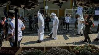 Petugas Satpol PP Kecamatan Larangan mensosialisasikan penggunaan masker dengan menggunakan kostum hantu pocong di Pasar Kreo, Kota Tangerang, Banten, Rabu (16/09)