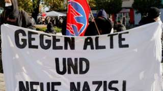 Protesters hold a banner reading 'Against Old And New Nazis!' during a counter-demonstration