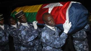 Togolese gendarmes carry di coffin of one of di victims of di attack, wrapped in di national flag
