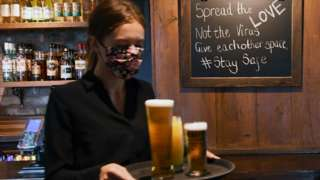 A staff member carries drinks to table at a pub in Chessington, Britain,
