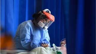 An NHS staff member wears PPE