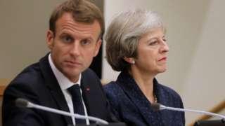 Emmanuel Macron, facing the camera, beside Theresa May, who is facing away