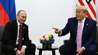 US President Donald Trump (R) attends a meeting with Russia's President Vladimir Putin