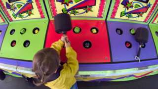 young girl playing whack-a-mole