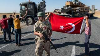 People hold a Turkish flag as they give their support to the Turkish military during the deployment of tanks to Syria