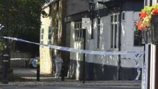 A forensics officer outside the pub